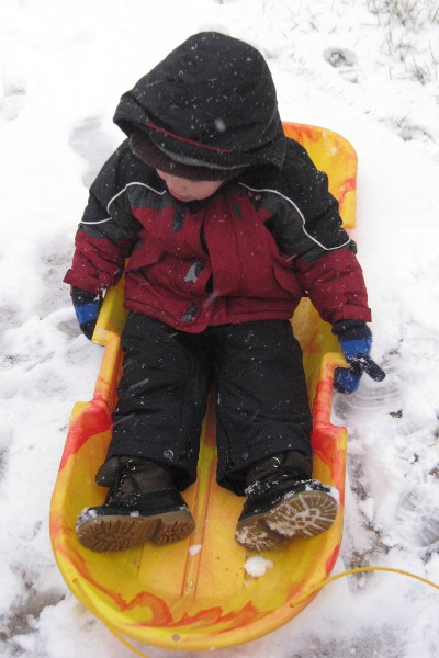 photo of a child sitting in a sled on some snow