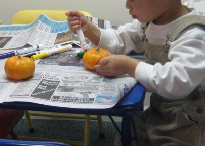picture of a child coloring a small pumpkin