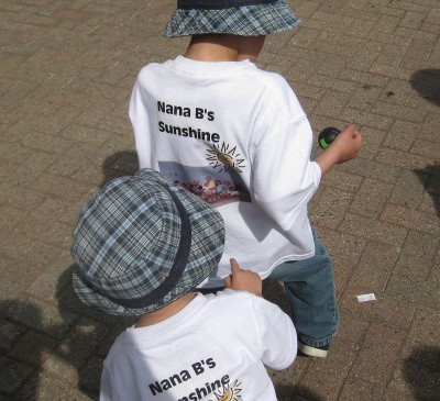 picture of a child looking at a family photo on the back of another kid's shirt