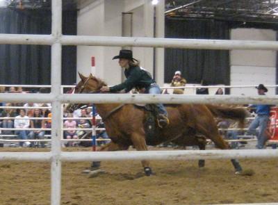 photo of rodeo horse racing around the slalom pole