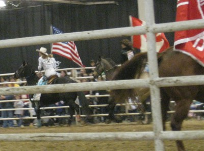 photo of rodeo horses parading the flags around the arena