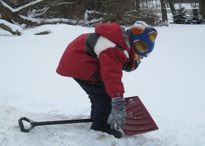 photo of a child using a shovel for a sled