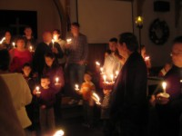 people singing by candlelight in a church