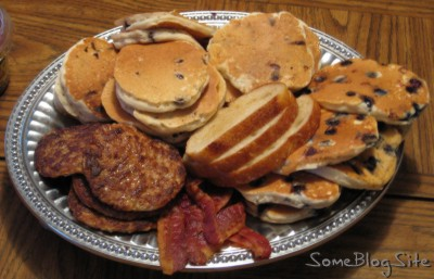 platter filled with breakfast food of pancakes, sausage, and bacon