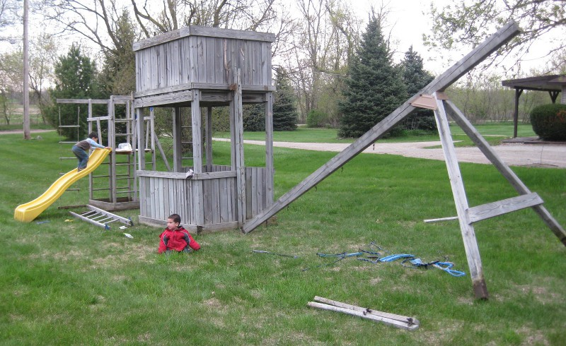 picture of a wooden play structure still needing some assembly