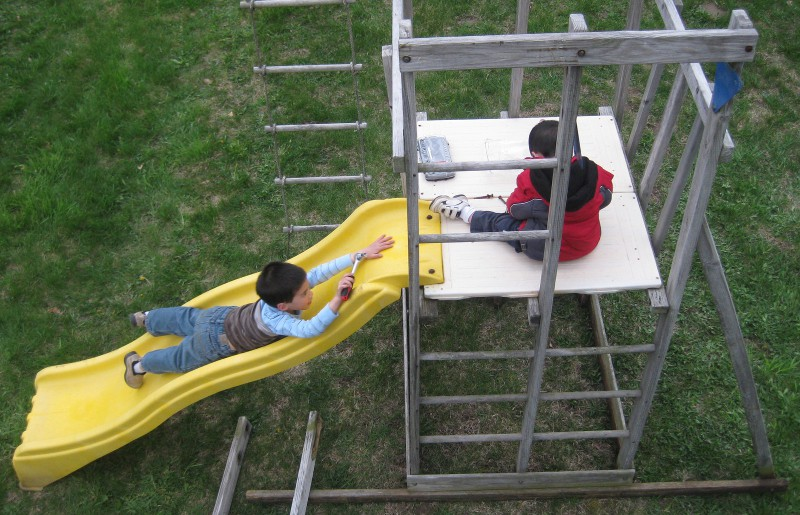 picture of a children helping assemble a wooden play fort