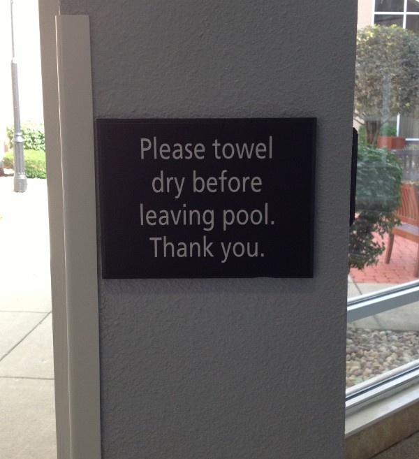 image of a sign at a hotel pool that says to towel dry before leaving pool