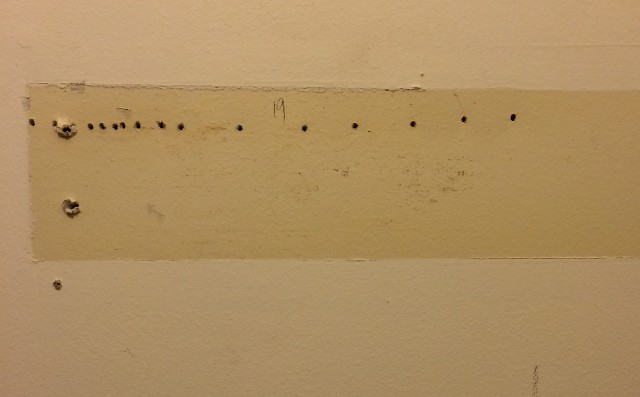 image of holes drilled in a wall to find the stud