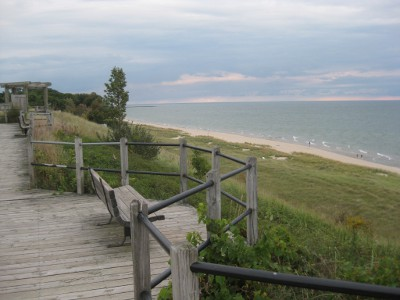 railing atop a hill overlooking a beach on Lake Michigan