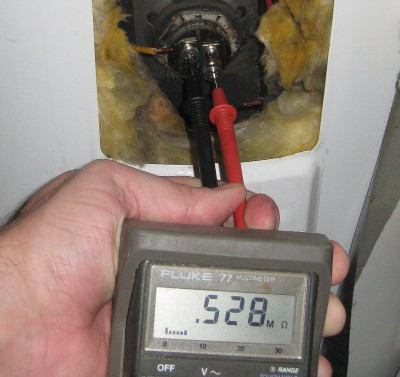 picture of a multimeter measuring resistance of a bad water heater element
