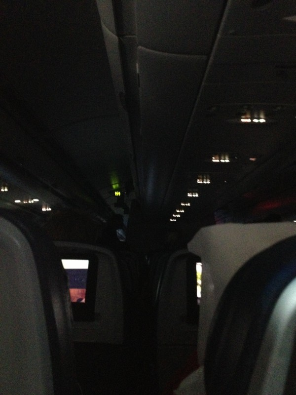 photo of the interior of an airplane that is darkened to allow people to watch their screen entertainment.