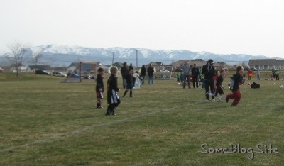 photo of children's soccer game with mountains in the background