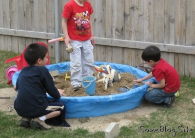 photo of children playing in a sandbox