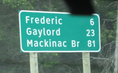 road sign showing the distance to the Mackinac Bridge