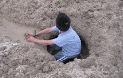 picture of a child digging a hole at the Lake Michigan beach at Maranatha
