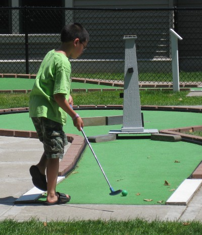 picture of a child playing mini golf
