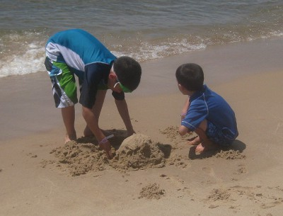 picture of children digging in the sand at the beach