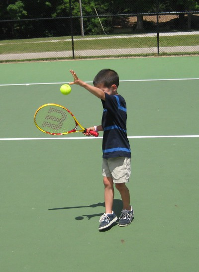 picture of a child serving a tennis ball