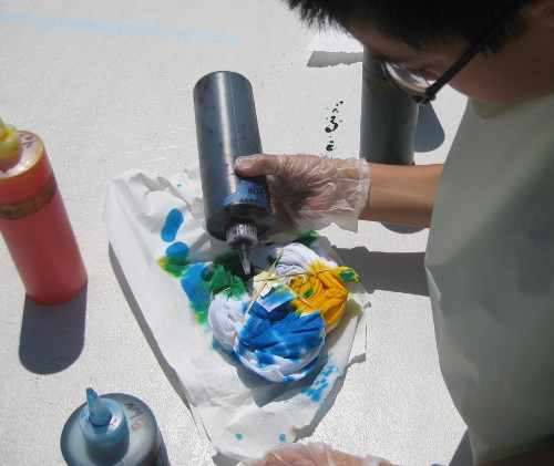 picture of a child making a tie-dye T-shirt at camp