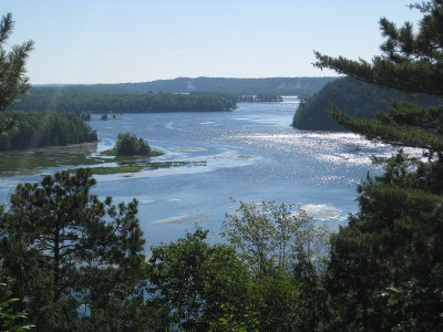 picture of the tree-lined Au Sable river with the sun sparkling on the waves