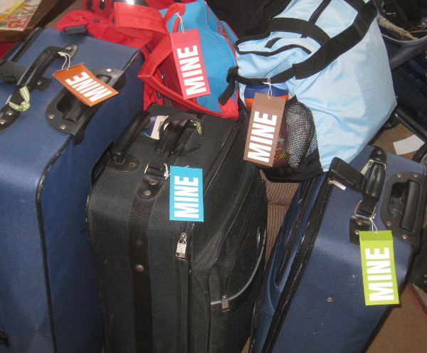 photo of luggage and suitcases with name tags that say 'mine'